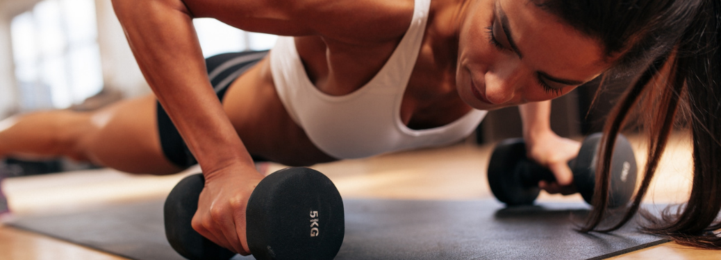woman in athletic gear doing pushup on yoga mat while holding dumbells
