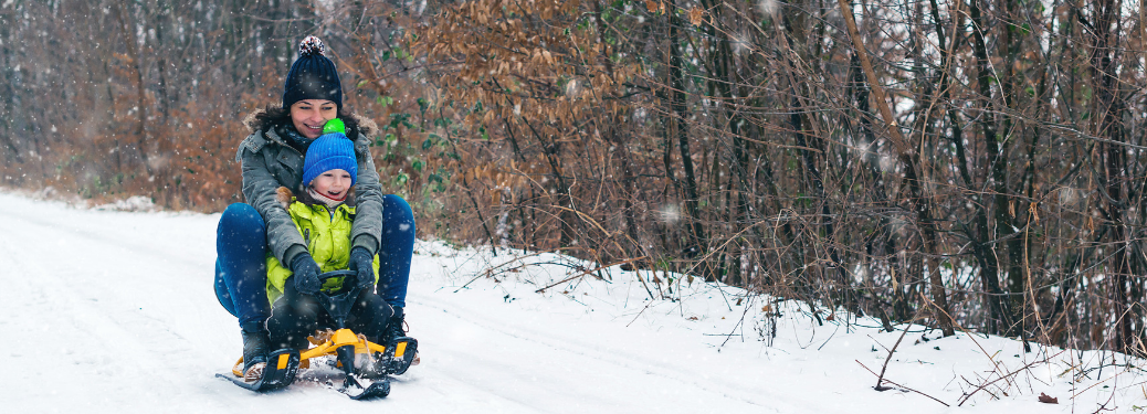 young woman and little girl sledding down hill on sled together