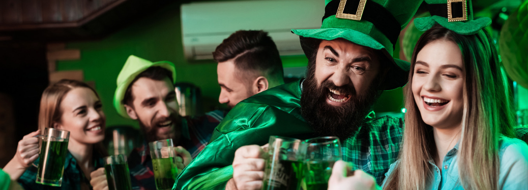 group of young people at bar wearing st. patrick's day costumes and drinking green beer