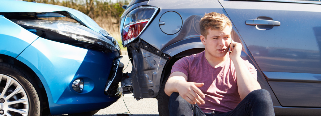 young boy on phone sitting next to two cars in rear-end collision