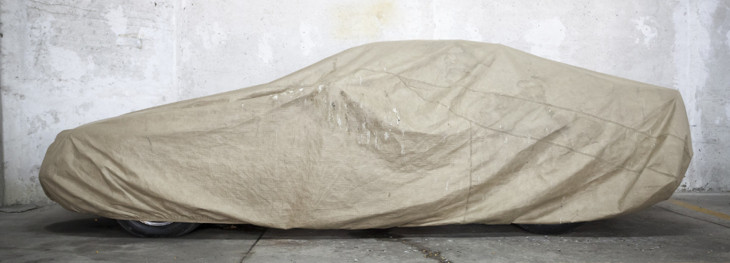 side view of covered car in garage