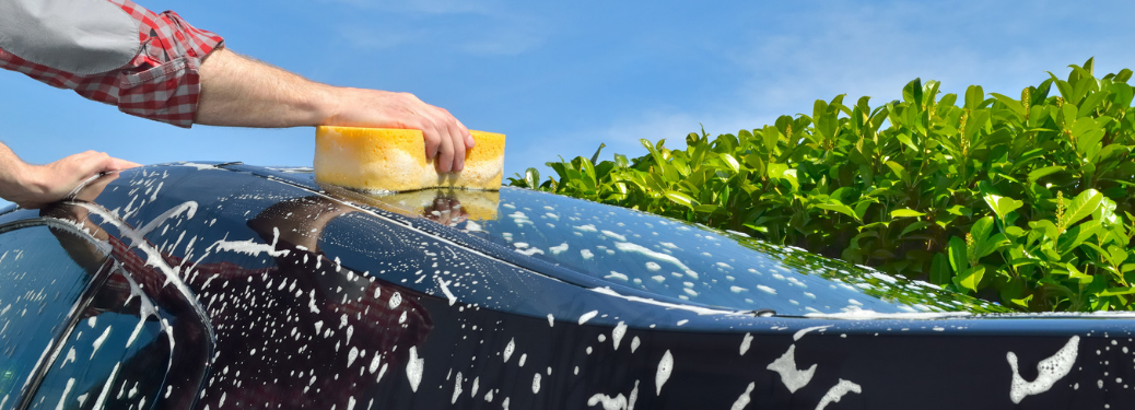 man cleaning exterior of car with sponge outside