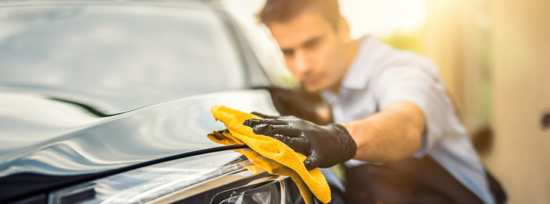 man wiping exterior of car with yellow cloth