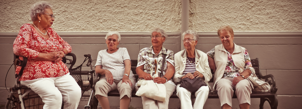 group of senior women sitting together on bench