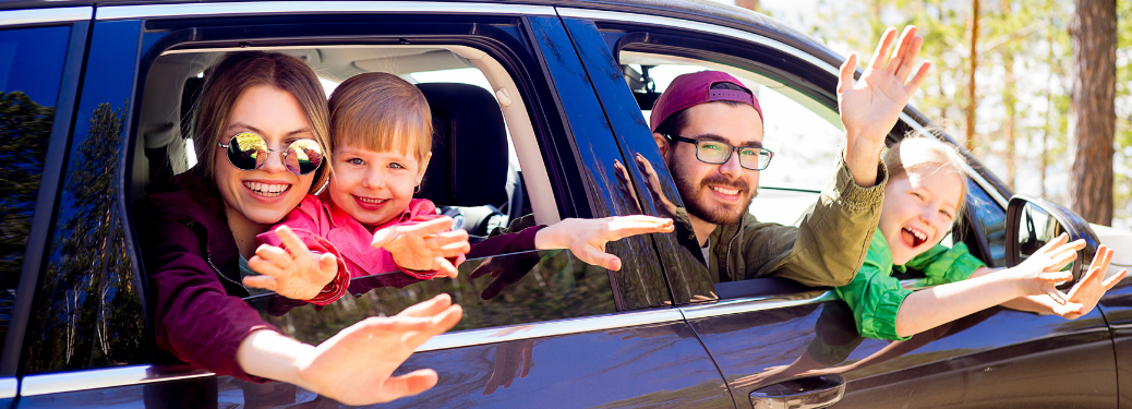 family with two kids waving out window of minivan