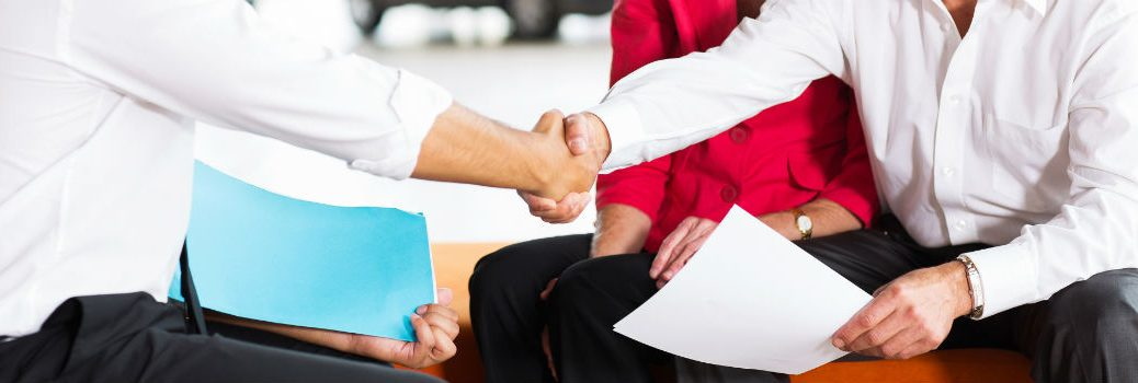 Car Salesman and Customers Shaking Hands Over Paperwork