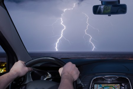 Person driving with lightning through the windshield