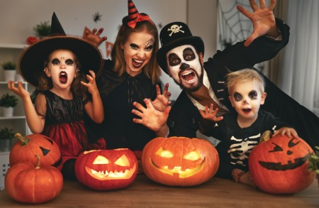 Family dressed up in Halloween costumes and making scary poses