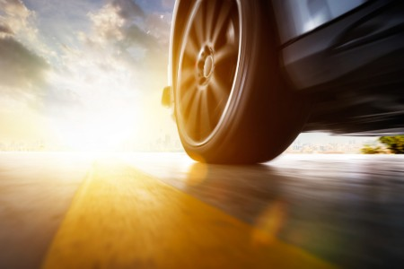 Close up of the front driver tire of a car driving down a road with a sunset in the background