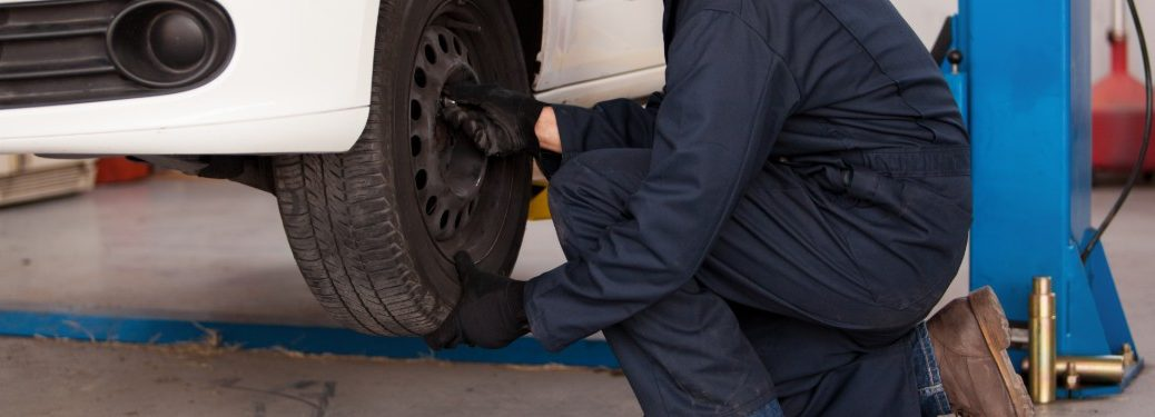 Close up of a mechanic rotating a tire on a white car