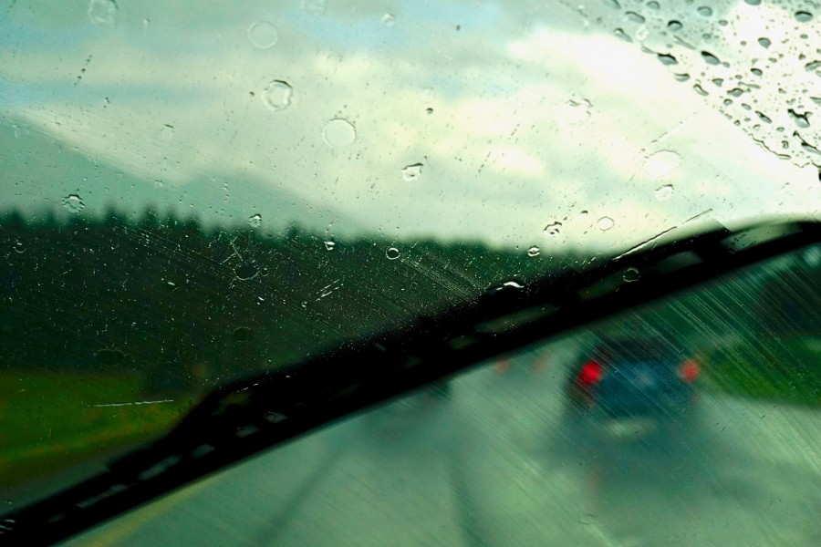 Driver view of a smearing windshield wiper being used in the rain