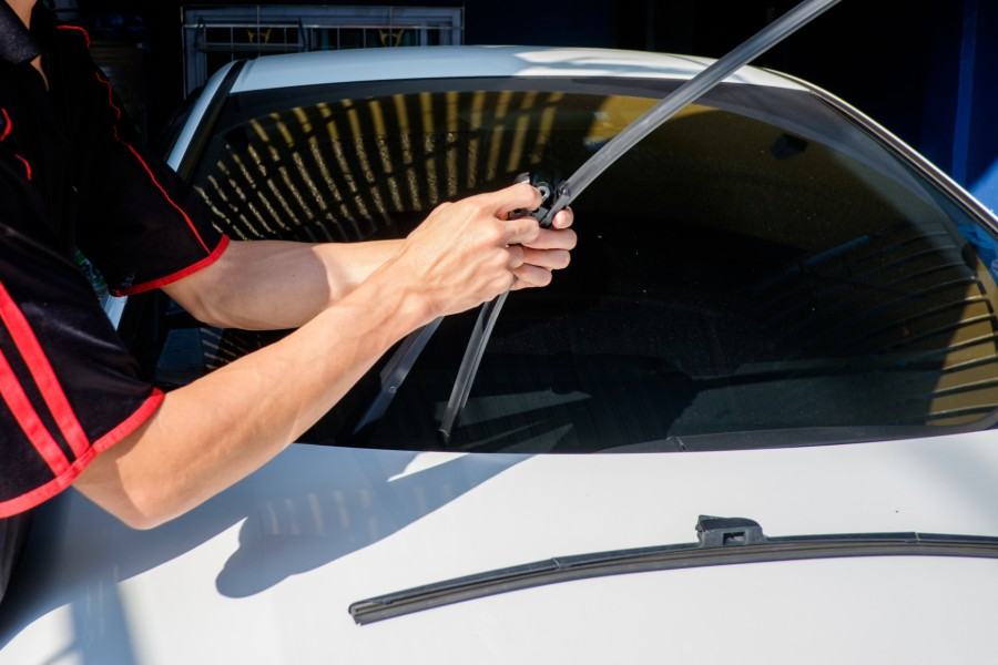 Close up of a mechanic replacing the wiper blades on a car