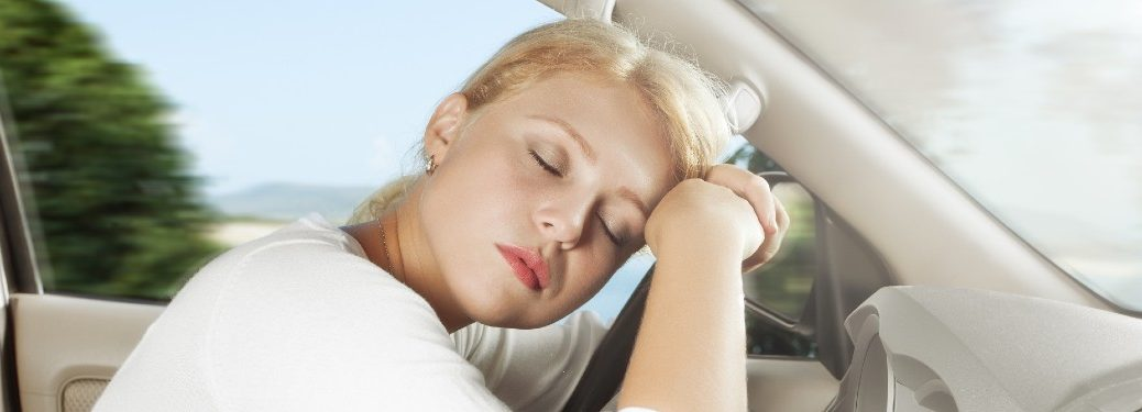 Woman asleep with her head on the steering wheel of her car