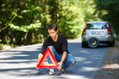 man setting reflective triangle on side of road with car in background