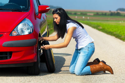 woman on side of road changing driver side front tire of red car