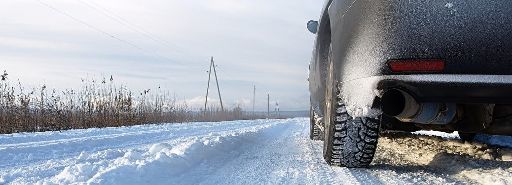 Close up of the tires of a car driving on a snowy road