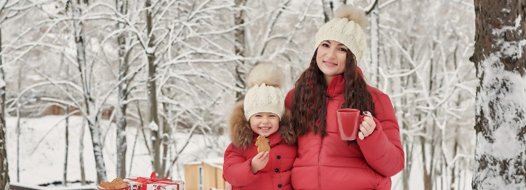 Mother and child dressing in winter clothing with snowy trees in the background while eating cookies and drinking hot chocolate