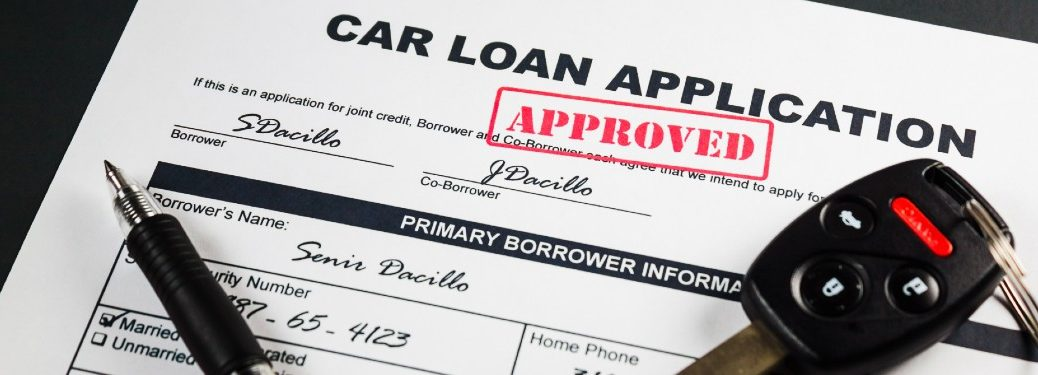 Close up of an approved car loan application with a pen and car keys on it
