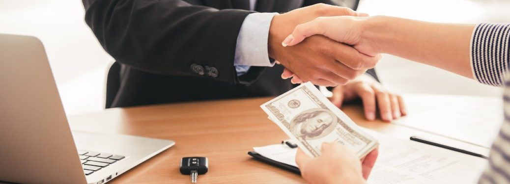 Close up of a woman holding cash and shaking hands with a salesman