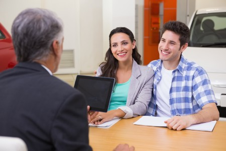Smiling couple speaking with a car salesman