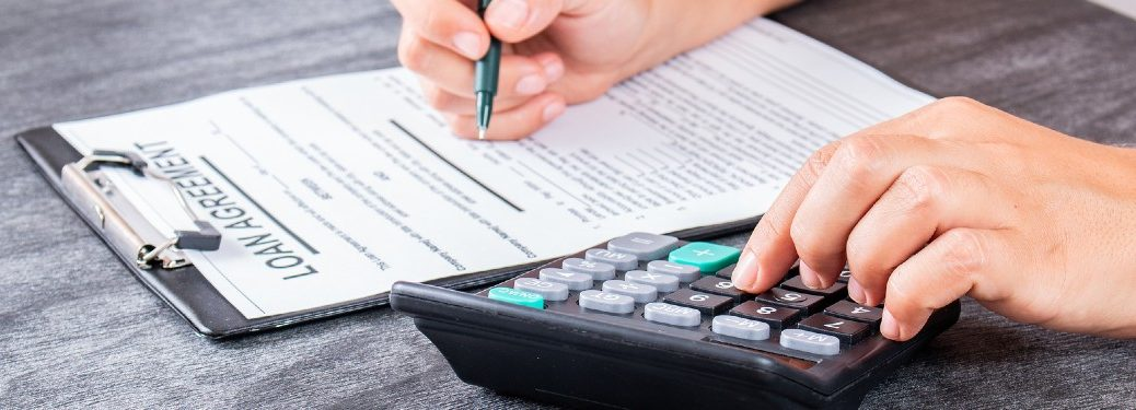 Close up of a person signing a loan with a calculator