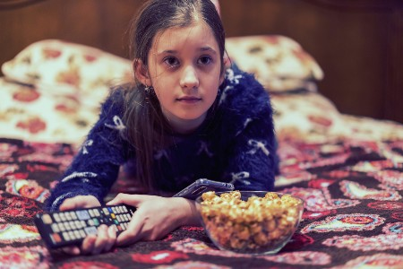 Girl on her bed with a tv remote and a bowl of popcorn