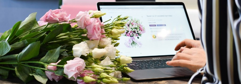 Woman on laptop with a bouquet of flowers next to her