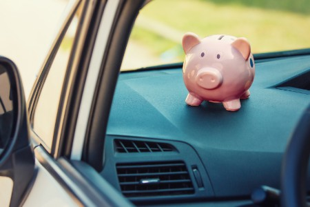 Piggy bank sitting on the dashboard inside a vehicle