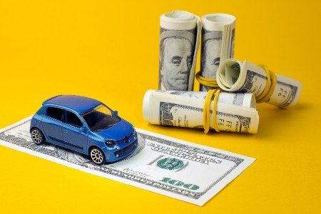 Blue toy car on top of a one-hundred dollar bill with more cash rolled up near it