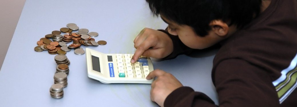 Young boy counting money with a calculator