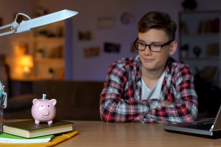 Teen boy with a laptop and books looking at a piggy bank