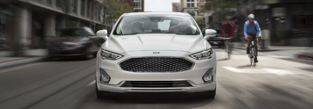 Front angle of a white 2020 Ford Fusion driving in a city