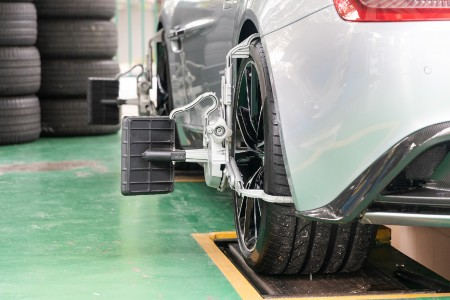 Rear angle of a white car getting its wheels aligned