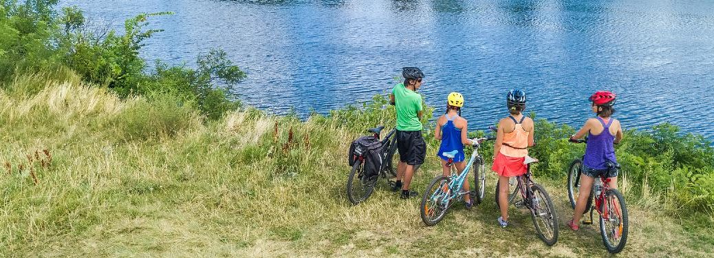 Family on bikes looking at a lake