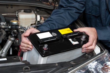 Mechanic replacing a car battery
