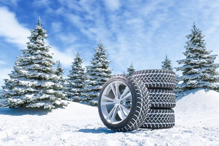 Snow tires stacked on top of snow with snowy trees in the background
