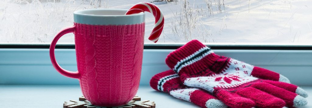 Red mug with a candy cane in it and a pair of gloves nearby