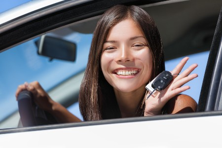 Happy teen driver sitting in the driver's seat with car keys in her hand