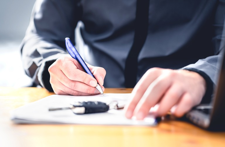 Person signing a form with car keys on top of the paper