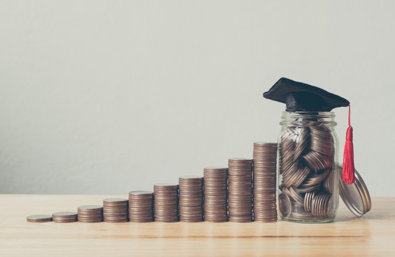 Coins stacked together with a graduation cap on top of a jar of coins