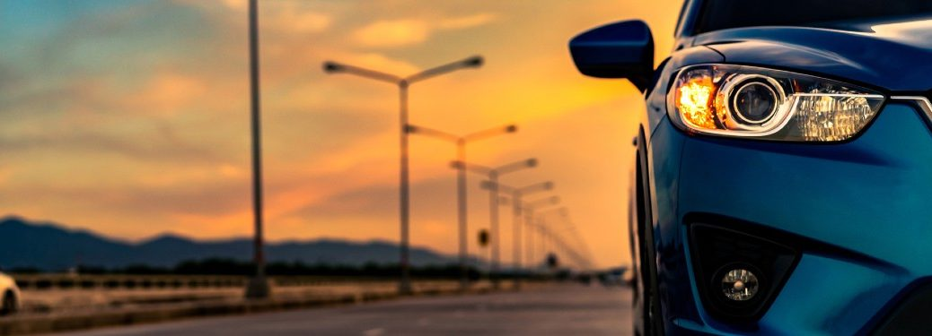 Close up of a blue car with a sunset in the background
