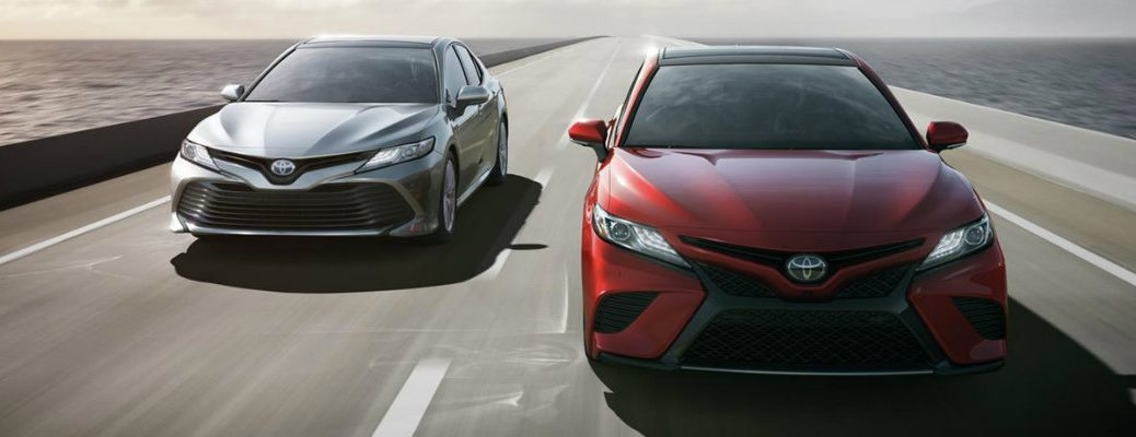 Two 2018 Toyota Camry models traveling down empty highway in daytime
