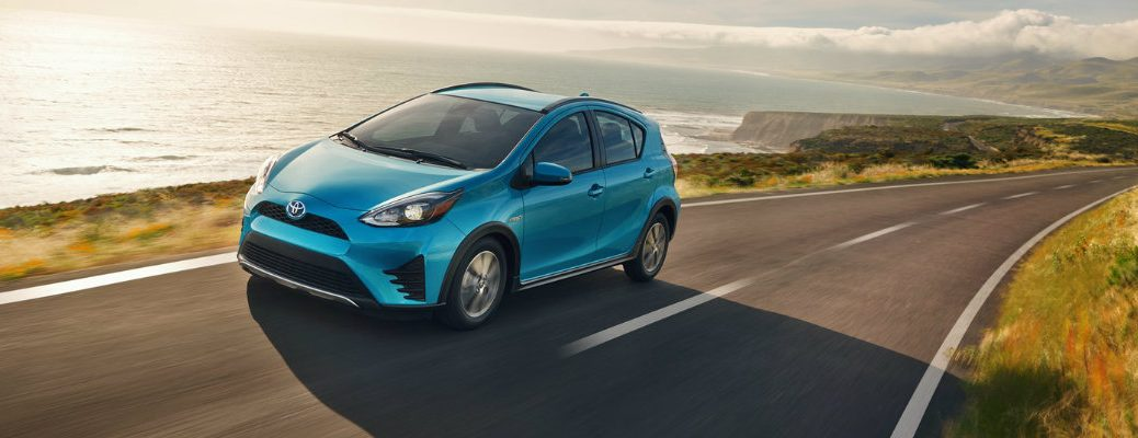 Teal Toyota Prius c driving down empty waterfront road in late afternoon
