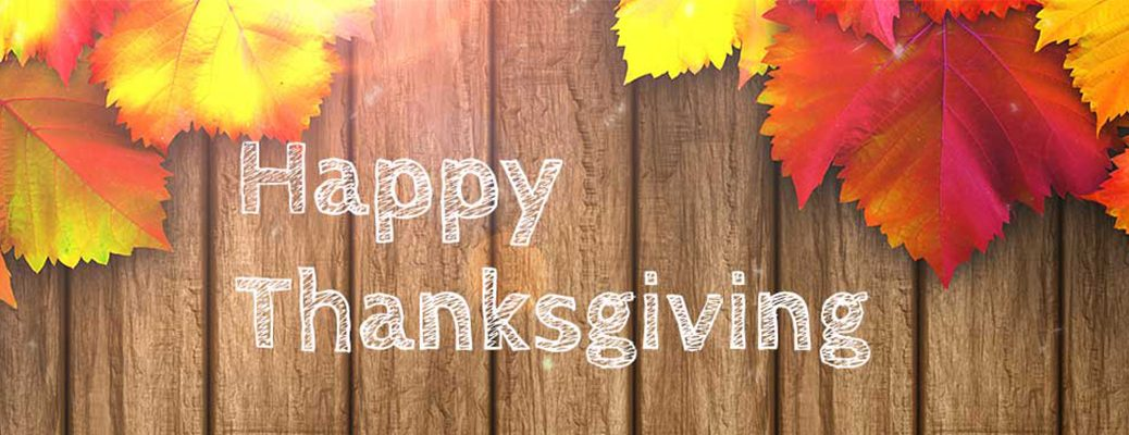 "Wood paneling and leaves on backdrop with ""Happy Thanksgiving"" written in center of photo"