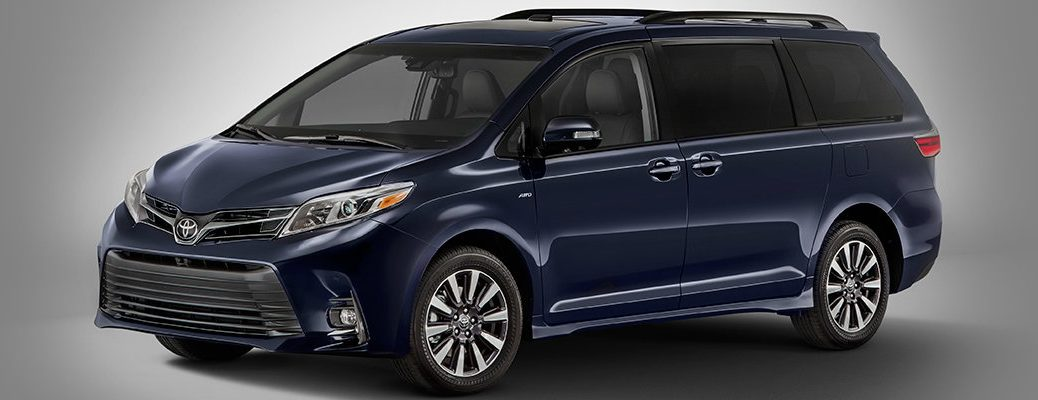 Side shot of blue 2018 Toyota Sienna on gray background with vehicle illuminated