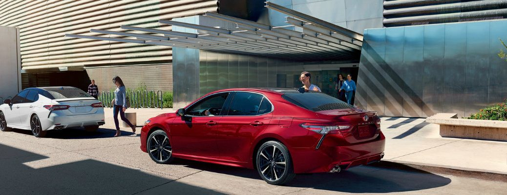 Two Toyota Camry models parked in front of abstractly constructed building