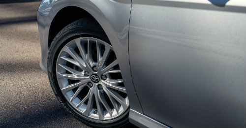 Front Door Panel Of Silver Toyota Camry With Tire Prominently Shown