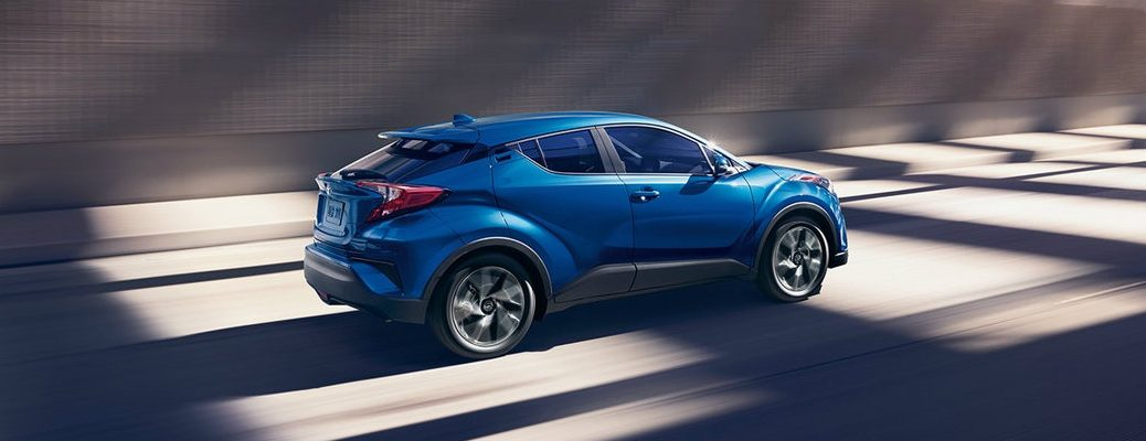 Long shot of blue 2018 Toyota C-HR driving down empty road