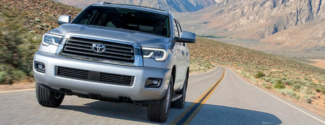 Silver 2018 Toyota Sequoia driving alone through desert road with mountain in background