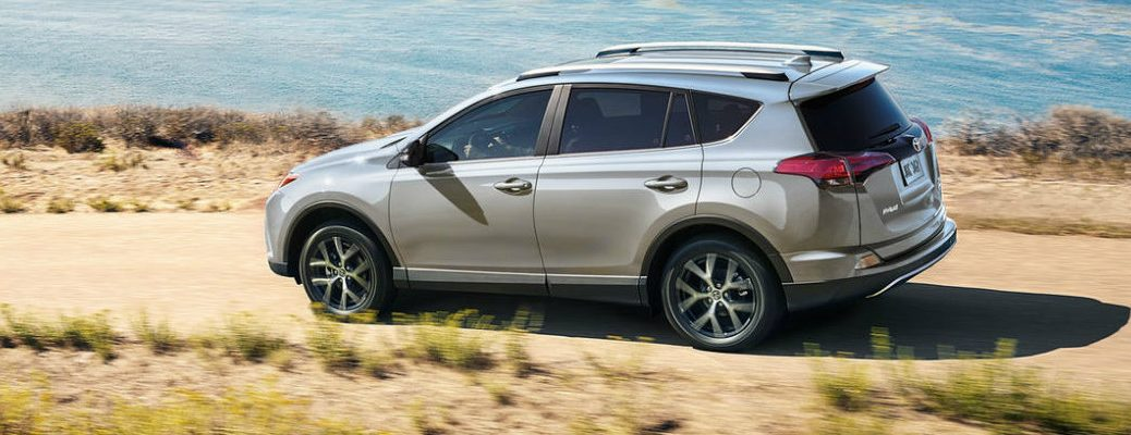 Silver Toyota RAV4 model driving down dirt waterfront road in daytime